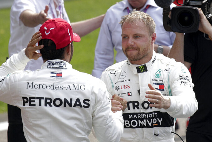 Mercedes driver Valtteri Bottas of Finland, right, is congratulated by his teammate Lewis Hamilton of Britain after taking pole position for the Chinese Formula One Grand Prix at the Shanghai International Circuit in Shanghai, China, Saturday, April 13, 2019. Hamilton finished second. (AP Photo/Andy Wong)