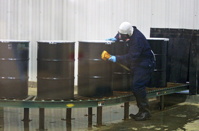 FILE - In this Monday, Dec. 9, 2013, file photo, a worker decontaminates steel drums containing yellowcake uranium to ensure safe shipment at UR Energy's Lost Creek uranium production facility in Sweetwater County, Wyo. The Trump administration is asking Congress for $1.5 billion over 10 years to build up a U.S. uranium stockpile, saying it wants to break an over-reliance on foreign uranium that undermines U.S. energy security. But some market analysts, Democrats and environmental organizations say the program, which would require congressional approval, is essentially a taxpayer bailout for a few uranium companies that can't compete in the global market. (Alan Rogers/The Casper Star-Tribune via AP, File)