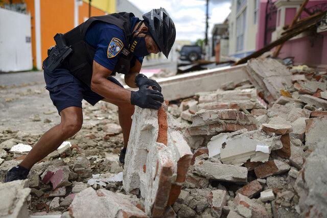 Un policía con una máscara protectora por el coronavirus, retira escombros dejados por un sismo de magnitud 5,4 en Ponce, Puerto Rico, el sábado, 2 de mayo del 2020. No hubo informes inmediatos de víctimas. (AP Foto/Carlos Giusti)