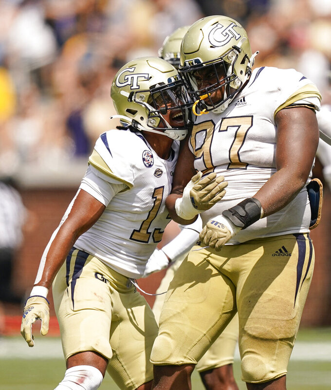 Georgia Tech defensive back Wesley Walker (13) congratulates defensive lineman Akelo Stone (97) after Stone sacked Kennesaw State quarterback Xavier Shepherd in the second half of an NCAA college football game, Saturday, Sept. 11, 2021, in Atlanta. (AP Photo/Brynn Anderson)
