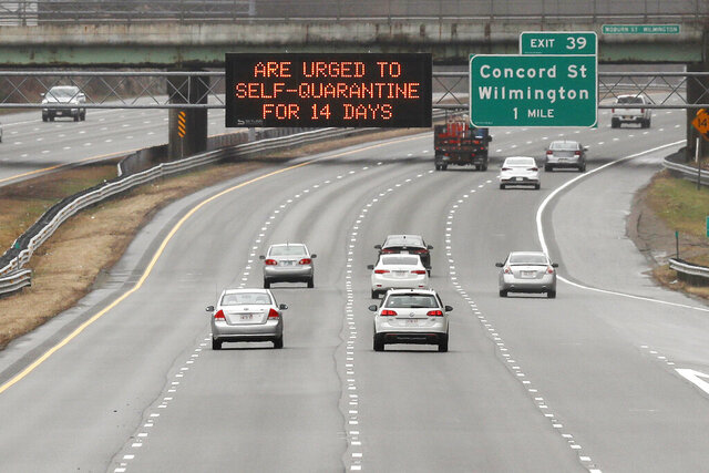 A highway sign urges out of state visitors to self-quarantine for 14 days if they plan on staying in Massachusetts due to the virus outbreak along Route 93 southbound in Wilmington, Mass., Monday, March 30, 2020. The new coronavirus causes mild or moderate symptoms for most people, but for some, especially older adults and people with existing health problems, it can cause more severe illness or death. (AP Photo/Charles Krupa)