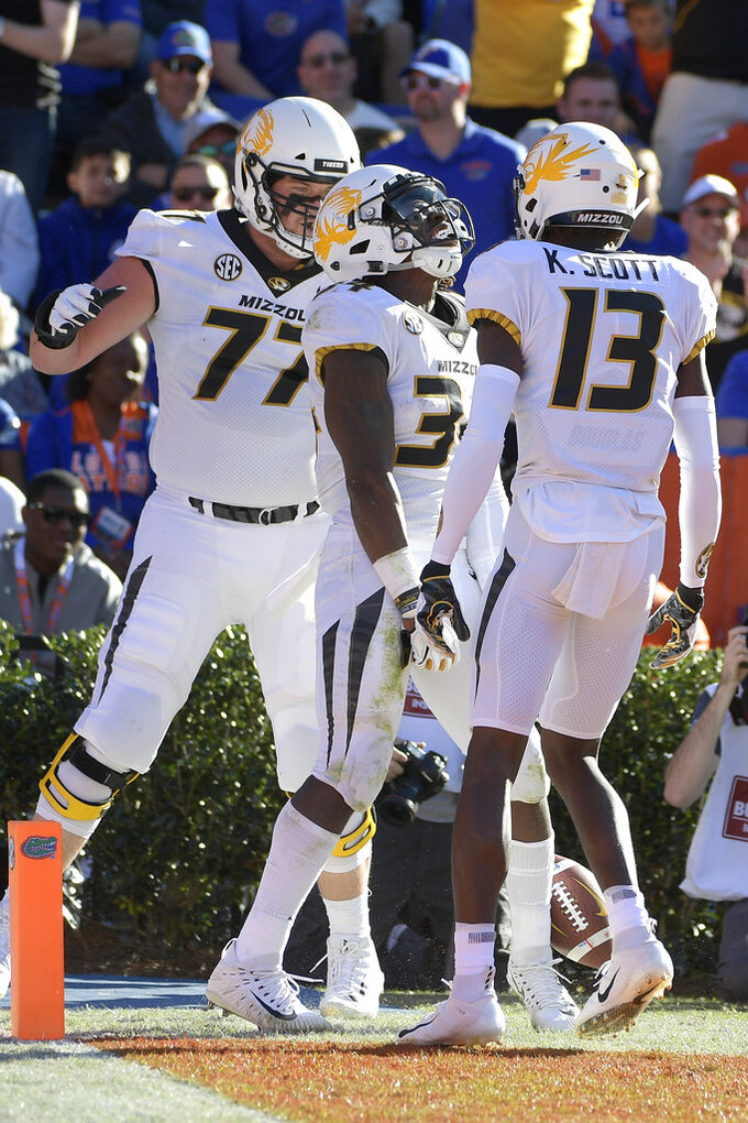 Missouri running back Larry Rountree III, center, celebrates with offensive lineman Paul Adams (77) and wide receiver Kam Scott (13) after rushing for a 27-yard touchdown during the first half of an NCAA college football game against Florida Saturday, Nov. 3, 2018, in Gainesville, Fla. (AP Photo/Phelan M. Ebenhack)