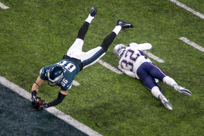 FILE - In this Feb. 4, 2018, file photo, Philadelphia Eagles tight end Zach Ertz (86) dives for a touchdown past New England Patriots safety Devin McCourty (32) in the fourth quarter of the NFL Super Bowl 52 football game in Minneapolis. The Eagles 41-33 victory celebration had to wait for a video review, which upheld that Ertz had already established possession of the ball before he bobbled it on the ground. (AP Photo/Bruce Kluckhohn, File