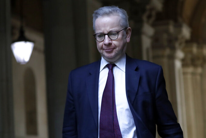 """FILE - In this Tuesday, Dec. 1, 2020 file photo, Michael Gove, Britain's Chancellor of the Duchy of Lancaster walks into Downing Street after attending a cabinet meeting in London. Britain's High Court has ruled that the U.K. government acted unlawfully in awarding a contract to a company run by friends of the former top adviser to Prime Minister Boris Johnson. A judge ruled Wednesday, June 9, 2021 that a June 2020 decision by Cabinet Office minister Michael Gove to pay more than 500,000 pounds ($700,000) to market research firm Public First """"gave rise to apparent bias and was unlawful."""" (AP Photo/Kirsty Wigglesworth, file)"""