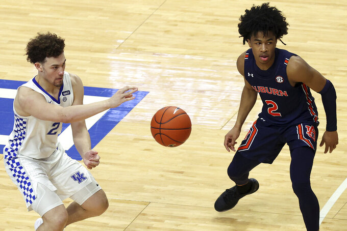 Kentucky's Devin Askew, left, passes away from Auburn's Sharife Cooper during the second half of an NCAA college basketball game in Lexington, Ky., Saturday, Feb. 13, 2021. Kentucky won 82-80. (AP Photo/James Crisp)