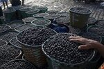 In this Sept. 7, 2019 photo, a vendor places his hand on acai berries at the Ver-o-Peso riverside market in Belém, Brazil. Belém is the epicenter for the trade of the oily purple acai that is a staple of native Amazon cuisine and a global superfood. (AP Photo/Rodrigo Abd)