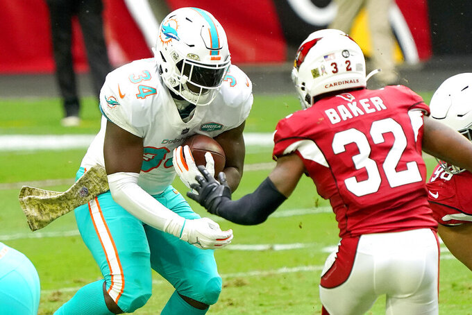 Miami Dolphins running back Jordan Howard (34) runs the ball as Arizona Cardinals strong safety Budda Baker (32) defends during the first half of an NFL football game, Sunday, Nov. 8, 2020, in Glendale, Ariz. (AP Photo/Rick Scuteri)
