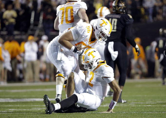 Tennessee quarterback Jarrett Guarantano (2) is helped up by offensive lineman Riley Locklear (56) after being knocked down in the second half of an NCAA college football game against Vanderbilt, Saturday, Nov. 24, 2018, in Nashville, Tenn. (AP Photo/Mark Humphrey)
