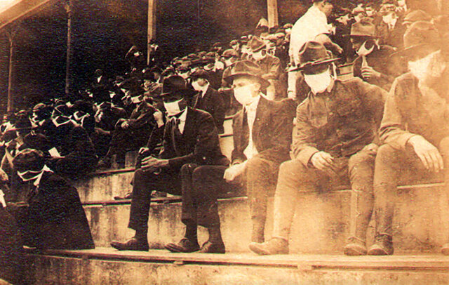 This undated photo provided by Georgia Tech alumnus Andy McNeil shows a Georgia Tech home game during the 1918 college football season. The photo was taken by Georgia Tech student Thomas Carter, who would receive a degree in Mechanical Engineering. The 102-year-old photo could provide a snapshot of sports once live games resume: Fans packed in a campus stadium in the midst of a pandemic wearing masks with a smidge of social distance between them on concrete seats. (Thomas Carter via AP)