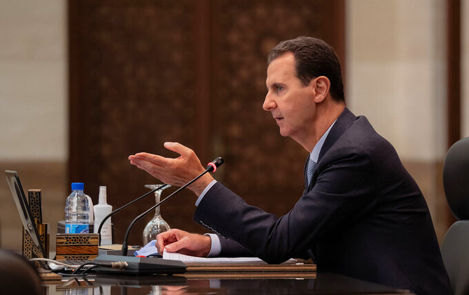 In this photo released on the official Facebook page of the Syrian Presidency, Syrian President Bashar Assad heads a cabinet meeting, in Damascus, Syria, Tuesday, March 30, 2021. Assad and his wife have recovered from COVID-19 and returned to their regular duties on Tuesday, three weeks after they had tested positive for the coronavirus, the president's office said. (Syrian Presidency Facebook page via AP)