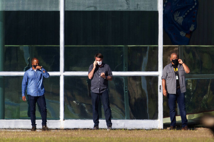 Brazil's President Jair Bolsonaro, center, talks on his phone while standing outside his official residence Alvorada Palace, in Brasilia, Brazil, Friday, July 10, 2020. Bolsonaro, 65, announced that he is infected with the new coronavirus on Tuesday and is using it to publicly extol hydroxychloroquine, the unproven malaria drug that he's been promoting as a treatment for COVID-19, and now takes himself. (AP Photo/Eraldo Peres)