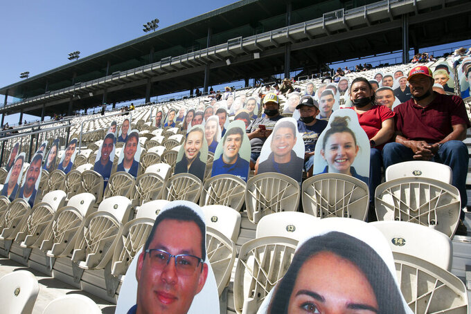Cardboard placards outnumber live fans before a NASCAR Cup Series race, Sunday, June 6, 2021, at Sonoma Raceway in Sonoma, Calif. California health officials are still enforcing COVID-19 protocols that include mask-wearing and social distancing. (AP Photo/D. Ross Cameron)