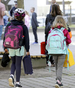 Children make their way to school by their parents in Rostock, Germany Monday, Aug. 3, 2020 as Mecklenburg-Western Pomerania is the first federal state to resume regular school operations throughout the state. About 150,000 students are expected to attend their schools. (Bernd Wuestneck/dpa via AP)