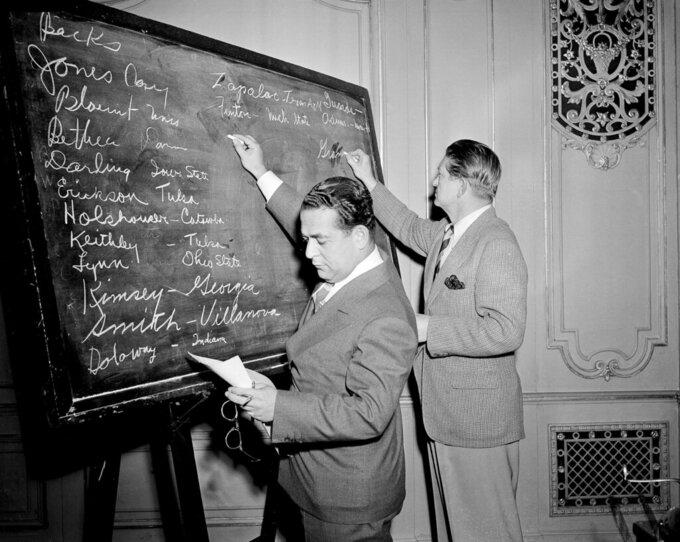 "FILE - In this April 18, 1943, file photo, Fred Mandel, foreground, president of the Detroit Lions, and Charles ""Chile"" Walsh, assistant coach of the Cleveland Rams, look over prospects at the player draft of the NFL in Chicago. The number of rounds fluctuated through the years, in part because of competition from the All-America Football Conference in the 1940s, but also because college football grew and more players were available.  (AP Photo/Harry L. Hall, File)"