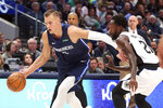 Dallas Mavericks forward Kristaps Porzingis (6) drives the ball against Los Angeles Clippers guard Patrick Beverley (21) during the first half of an NBA basketball game Tuesday, Jan. 21, 2020 in Dallas. (AP Photo/Richard W. Rodriguez)
