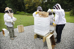 In this Aug. 7, 2019 photo, instructor Karen Eaton, left, supervises beekeeping activities performed by veterans at the Veterans Affairs' beehives in Manchester, N.H. New Hampshire's only veterans medical center is hoping its beekeeping program will help veterans deal with their trauma. A small but growing number of veterans around the country are turning to beekeeping as a potential treatment for anxiety, PTSD and other conditions. (AP Photo/Elise Amendola)