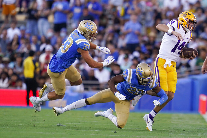 LSU quarterback Max Johnson (14) is tackled by UCLA defensive back Obi Eboh (22) during the first half of an NCAA college football game Saturday, Sept. 4, 2021, in Pasadena, Calif. (AP Photo/Marcio Jose Sanchez)