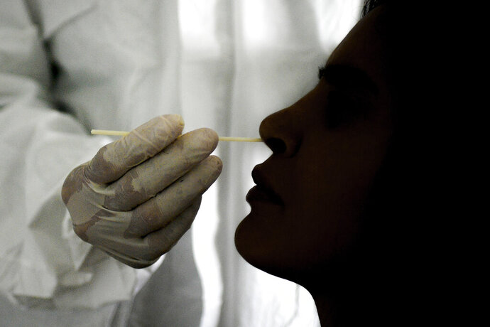 FILE - In this Sept. 19, 2020 file photo, a doctor takes a nasal swab sample to test for COVID-19 at the Cocodrilos Sports Park in Caracas, Venezuela. PAHO, the regional office for the World Health Organization in the Americas, said the week of Jan. 22 2021 that only 3,000, or about 1%, of the 340,000 COVID antigen testing kits sent to the country have been used. (AP Photo/Matias Delacroix, File)