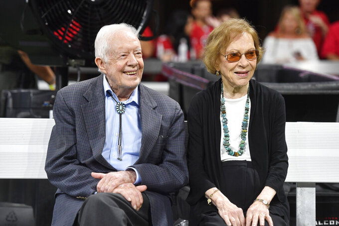 FILE- In this Sept. 30, 2018 file photo, former President Jimmy Carter and Rosalynn Carter are seen ahead of an NFL football game between the Atlanta Falcons and the Cincinnati Bengals, in Atlanta.  Former President Jimmy Carter and former first lady Rosalynn Carter will not attend President-elect Joe Biden's inauguration. It marks the first time the couple, 96 and 93, will have missed the ceremonies since Carter was sworn-in as the 39th president in 1977.(AP Photo/John Amis, File)