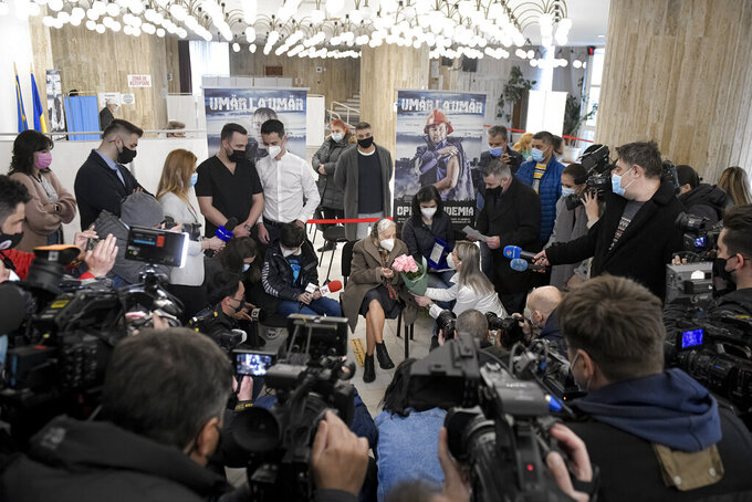 Zoea Baltag, center, receives flowers from a local administration official, while being surrounded by the media after getting her second dose of the Pfizer COVID-19 vaccine in Bucharest, Romania, Sunday, March 28, 2021. A 104-year-old Romanian woman received her second vaccine dose against COVID-19, becoming the oldest person in Romania's capital Bucharest to be fully inoculated against the disease. (AP Photo/Andreea Alexandru)