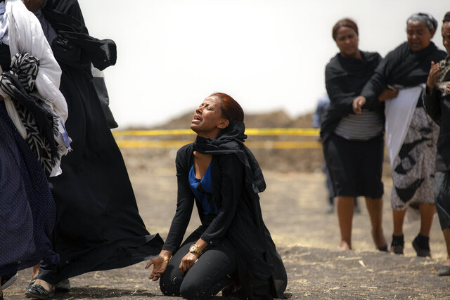 FILE - In this March 14, 2019 file photo, relatives of crash victims mourn at the scene where an Ethiopian Airlines Boeing 737 Max 8 passenger jet crashed shortly after takeoff, killing all 157 on board, near Bishoftu, in Ethiopia. These African stories captured the world's attention in 2019 - and look to influence events on the continent in 2020. (AP Photo/Mulugeta Ayene, File)