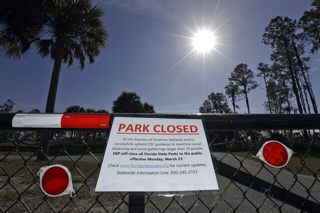 A closed sign, attached on the outside fence at the Alafia River State Park, is shown Monday, March 23, 2020, in Lithia, Fla. Florida Gov. Ron DeSantis has issued an order closing all of Florida's 175 state parks, trails and historic sites to help stop the spread of the coronavirus. (AP Photo/Chris O'Meara)