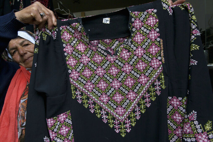 In this Monday, Jan. 28, 2019 photo, Samiha Jeheshat, displays a handmade embroidered Palestinian thobe at her showroom in the West Bank village of Idna, north of Hebron. The thobe is gaining prominence as a softer symbol of Palestinian nationalism, competing with the classic keffiyeh. Rashida Tlaib proudly wore her thobe to her historic swearing-in as the first Palestinian American member of Congress, inspiring women around the world to tweet photos of themselves in their ancestral robes. (AP Photo/Nasser Nasser)