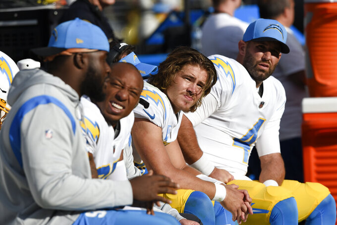 Los Angeles Chargers quarterbacks Justin Herbert, center, and Chase Daniel, right, sit on the bench with teammates during the second half of an NFL football game against the Baltimore Ravens, Sunday, Oct. 17, 2021, in Baltimore. The Ravens won 34-6. (AP Photo/Gail Burton)