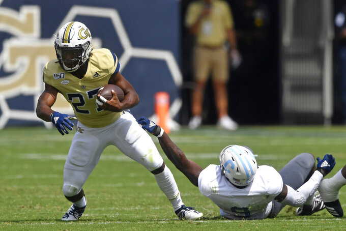 Georgia Tech running back Jordan Mason (27) shakes Citadel linebacker Willie Eubanks III (9) loose during the first half of an NCAA college football game, Saturday, Sept. 14, 2019, in Atlanta. (AP Photo/Mike Stewart)