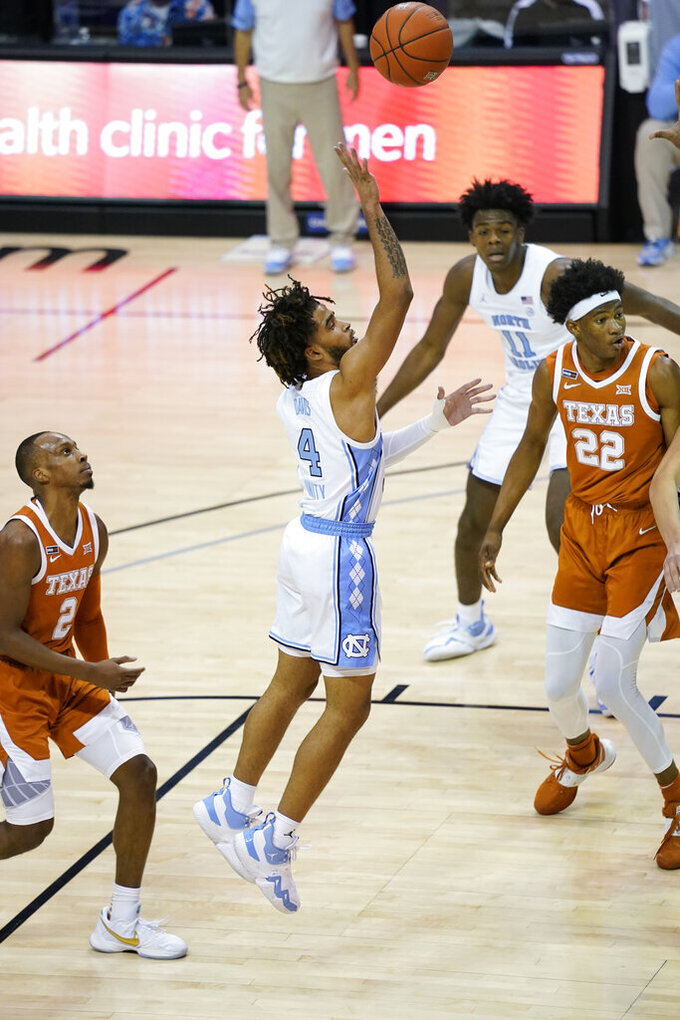 North Carolina guard R.J. Davis (4) shoots as Texas guard Matt Coleman III (2) and forward Kai Jones (22) watch during the second half of an NCAA college basketball game for the championship of the Maui Invitational, Wednesday, Dec. 2, 2020, in Asheville, N.C. (AP Photo/Kathy Kmonicek)