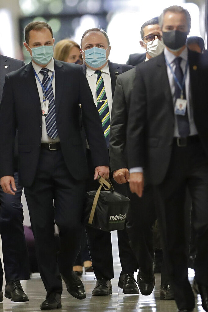 Brazil's former Health Minister Eduardo Pazuello, behind center, arrives at the Senate to testify in an investigation of the government's management of the COVID-19 pandemic in Brasilia, Brazil, Wednesday, May 19, 2021. (AP Photo/Eraldo Peres)