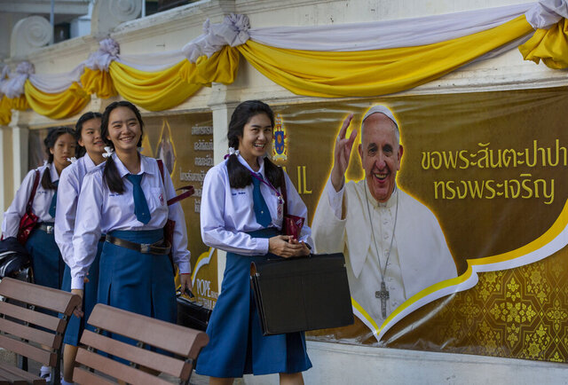 School children walk in Assumption Cathedral courtyard, decorated with posters of Pope Francis in Bangkok, Thailand, Wednesday, Nov. 20, 2019. Pope Francis arrives in Thailand on Wednesday for the first visit here by the head of the Roman Catholic Church since St. John Paul II in 1984. (AP Photo/Gemunu Amarasinghe)