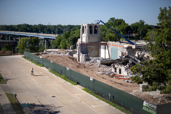A church is demolished where the oil services firm U.S. Ventures announced it would build a new headquarters employing 500 people on a city bluff in Appleton, Wis., Aug. 19, 2020. Then the coronavirus pandemic struck. The status of the U.S. Ventures headquarters is now uncertain, but even as the old church on the bluff gets demolished for a groundbreaking the headquarters certainly won't open as announced in 2022. (AP Photo/David Goldman)