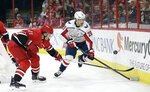 Washington Capitals' Lars Eller (20), of Denmark, and Carolina Hurricanes' Lee Stempniak (21) chase the puck during the first period of an NHL hockey game in Raleigh, N.C., Friday, Jan. 12, 2018. (AP Photo/Gerry Broome)