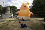 In this photo taken on Tuesday, July 10, 2018,  Ruth Armitage and her nine-month old baby Ivy pose for the media in front of a six-meter high cartoon baby blimp of U.S. President Donald Trump during a practice session in Bingfield Park, north London. Trump will get the red carpet treatment on his brief visit to England that begins Thursday: Military bands at a gala dinner, lunch with the prime minister at her country place, then tea with the queen at Windsor Castle before flying off to one of his golf clubs in Scotland. But trip planners may go out of their way to shield Trump from viewing another aspect of the greeting: an oversize balloon depicting the president as an angry baby in a diaper that will be flown from Parliament Square during what are expected to be massive gatherings of protesters opposed to Trump's presence. (AP Photo/Matt Dunham)
