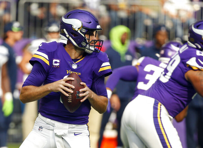 Minnesota Vikings quarterback Kirk Cousins, left, prepares to throw against the Seattle Seahawks in the first half of an NFL football game in Minneapolis, Sunday, Sept. 26, 2021. (AP Photo/Bruce Kluckhohn)