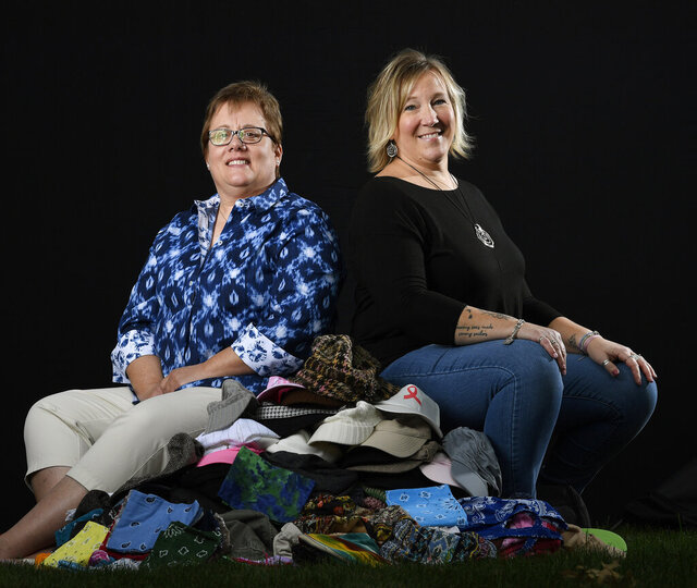 "Cancer survivors Nancy Beauregard, left, and April Good, right, both from Manheim Township, pose with hundreds of hats, scarves and bandana's that make up the Traveling Bag of Hats, in Manheim Township, Pa., Thursday, Oct. 1, 2020. Over the past nine years, the ""traveling bag of hats"" has helped six women who have lost their hair while battling cancer.  (Chris Knight/LNP/LancasterOnline via AP)"