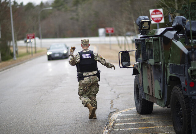 A member of the Rhode Island National Guard Military Police directs a motorist with New York license plates at a checkpoint on I-95 near the border with Connecticut where New Yorkers must pull over and provide contact information and are told to self-quarantine for two weeks, Saturday, March 28, 2020, in Hope Valley, R.I. Rhode Island Gov. Gina Raimondo on Saturday ordered anyone visiting the state to self-quarantine for 14 days and restricted residents to stay at home and nonessential retail businesses to close Monday until April 13 to help stop the spread of the coronavirus. (AP Photo/David Goldman)