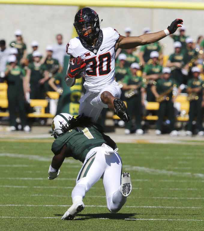 Oklahoma State's running back Chuba Hubbard, top, leaps over Baylor's safety Verkedric Vaughns in the second half of an NCAA college football game, Saturday, Nov. 3, 2018, in Waco, Texas. (Rod Aydelotte/Waco Tribune-Herald via AP)