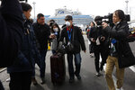 An unidentified passenger is surrounded by the media after he disembarked from the quarantined Diamond Princess cruise ship Wednesday, Feb. 19, 2020, in Yokohama, near Tokyo. Passengers tested negative for COVID-19 started disembarking Wednesday. (AP Photo/Jae C. Hong)