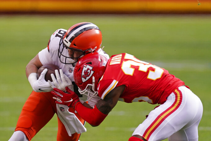 Cleveland Browns tight end Austin Hooper is tackled by Kansas City Chiefs cornerback Charvarius Ward, right, during the first half of an NFL divisional round football game, Sunday, Jan. 17, 2021, in Kansas City. (AP Photo/Charlie Riedel)