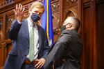 Matt Ritter, left, Speaker of the Connecticut House of Representatives, confers with Vincent Candelora, Republican Minority Leader in the Connecticut House, during a break in House debate on bill to legalize the recreational use of marijuana, Wednesday, June 16, 2021, in Hartford, Conn. (Mark Mirko/Hartford Courant via AP)
