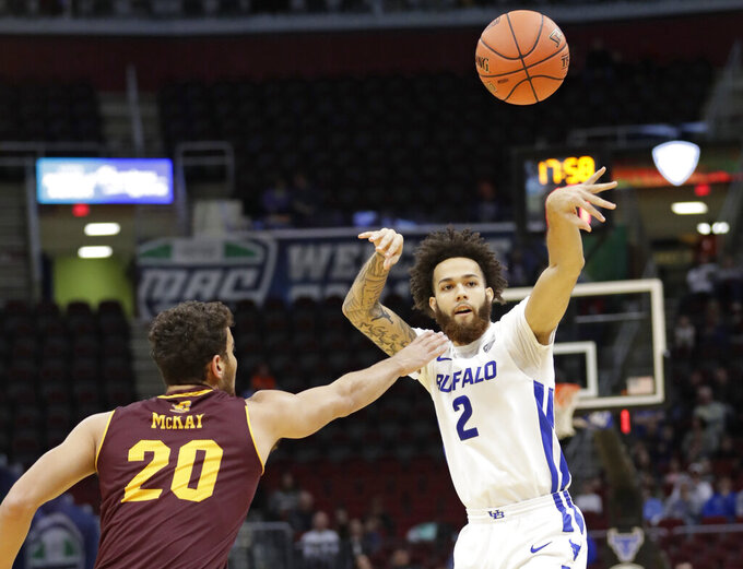 Buffalo's Jeremy Harris (2) passes against Central Michigan's Kevin McKay (20) during the first half of an NCAA college basketball game in the semifinals of the Mid-American Conference men's tournament Friday, March 15, 2019, in Cleveland. (AP Photo/Tony Dejak)