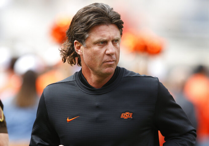 "FILE - In this Oct. 6, 2018, file photo, Oklahoma State football coach Mike Gundy runs onto the field before the team's NCAA college football game against Iowa State in Stillwater, Okla. Mike Holder, Oklahoma State's athletic director, said late Thursday, July 2, 2020, an internal review had found ""no sign or indication of racism"" in the football program under Gundy after a number of players raised concerns. (AP Photo/Sue Ogrocki, File)"