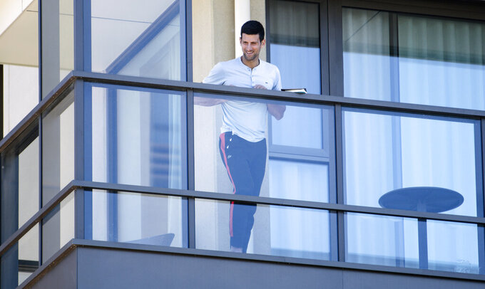 Serbia's Novak Djokovic stands on the balcony at his accommodation in Adelaide, Australia, Tuesday, Jan. 19, 2021. Australian Open tournament director Craig Tiley defended Djokovic for appealing to Australian Open organizers to ease restrictions so players could move to private residences with tennis courts. (Morgan Sette/AAP Image via AP)