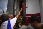 FILE - In this Wednesday, Jan. 8, 2020 file photo, residents receive aid supplies after suffering the previous day's magnitude 6.4 quake in Yauco, Puerto Rico. A key U.N. aid agency says needs for humanitarian assistance have ballooned this year because of COVID-19, projecting that a staggering 235 million people — who together would make up the world's fifth most-populous country — are likely to require such help next year for troubles like the pandemic as well as war, forced migration and the impact of global warming. (AP Photo/Carlos Giusti, file)
