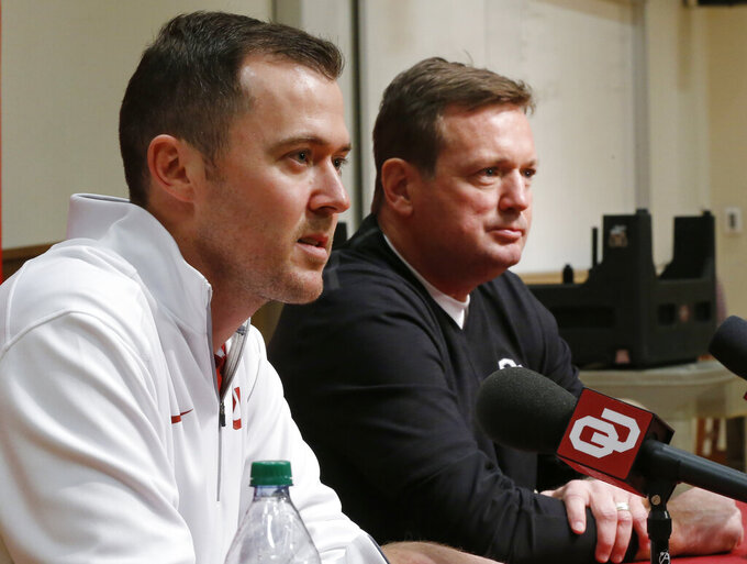FILE - Oklahoma offensive coordinator Lincoln Riley, left, answers a question during a news conference in Norman, Okla., as Oklahoma head coach Bob Stoops, right, looks on, in this Saturday, Jan. 17, 2015, file photo. Former Oklahoma coach Bob Stoops returned to the practice field this week to help his successor, Lincoln Riley, after virus issues led the five-time defending Big 12 champions to pause team activities last week, and postpone a game at West Virginia. (AP Photo/Sue Ogrocki, File