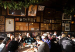 In this Dec. 27, 2019 photo, customers sit beneath vintage photos and documents, including a poster of Vice President Theodore Roosevelt, in McSorley's Old Ale House in New York. Located in Manhattan's Lower East Side, McSorley's opened in the mid-19th century and functioned as a speakeasy during Prohibition. (AP Photo/Mark Lennihan)