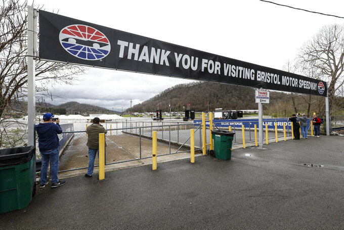 John Cody, left, and Bob Sampson from Cedarville, Ohio, left, take a photo of water flooding the vendor area is seen as races for both the Truck Series and NASCAR Cup Series auto race was postponed due to inclement weather at Bristol Motor Speedway, Sunday, March 28, 2021, in Bristol, Tenn. (AP Photo/Wade Payne)