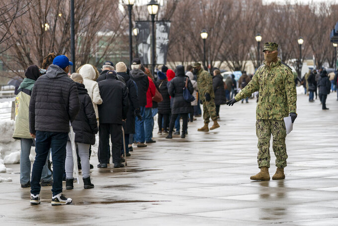A member of the National Guard gives people direction standing in line at a COVID-19 vaccination site at Yankee Stadium, Friday, Feb. 5, 2021, in the Bronx borough of New York. Yankee Stadium opened as a COVID-19 vaccination site Friday, drawing lines of people from surrounding neighborhoods in the Bronx. The mega-site is being restricted to Bronx residents as a way to boost vaccination rates in the New York City borough with the highest percentage of positive coronavirus test results. (AP Photo/Mary Altaffer)